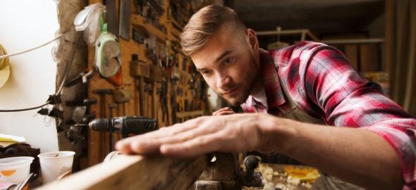 jeune homme travaillant le bois