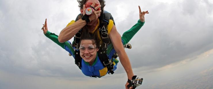 Un non-voyant saute en parachute accroché sur le dos de son instructeur, les deux sourient et le non-voyant se masque les yeux.