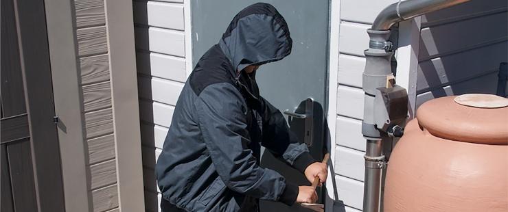 un voleur force une porte avec un pied de biche