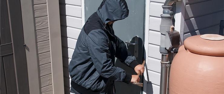 voleur qui essaie de forcer une porte